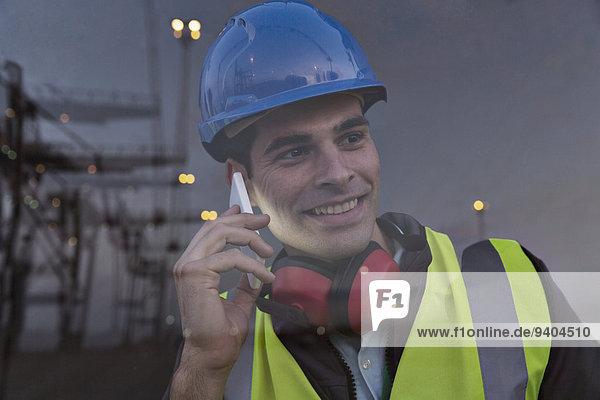 Arbeiter spricht am Handy in der Nähe des Fensters