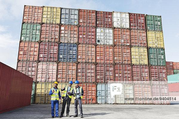 Arbeiter und Geschäftsleute im Gespräch in der Nähe von Frachtcontainern