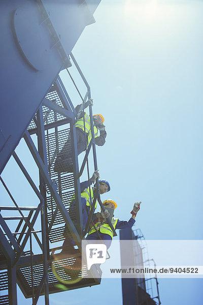 Niederwinkelansicht von Arbeitern und Geschäftsleuten am Ladekran