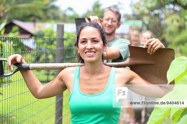 Lächelnde Frau in grünem Tank Top mit Schaufel auf den Schultern durch den Gemeinschaftsgarten