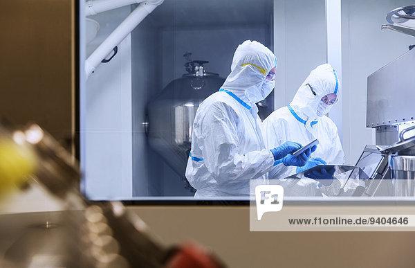 Wissenschaftler in sauberen Anzügen mit digitalen Tabletten im Laborversuch