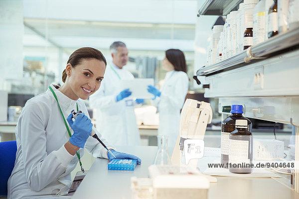 Wissenschaftler pipettieren Proben in den Tray im Labor