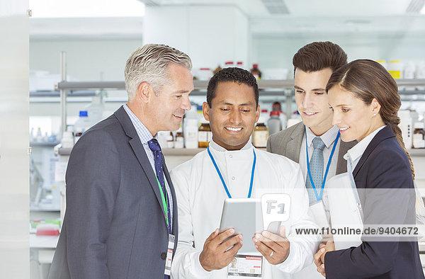 Wissenschaftler und Geschäftsleute  die Tablet PCn im Labor verwenden