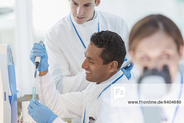 Wissenschaftler pipettieren Probe in Reagenzglas im Labor