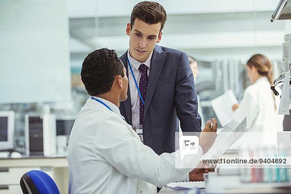 Wissenschaftler und Geschäftsmann im Gespräch im Labor