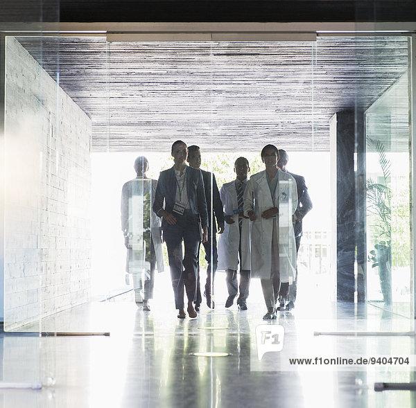 Wissenschaftler und Geschäftsleute bei der Annäherung an Glastüren