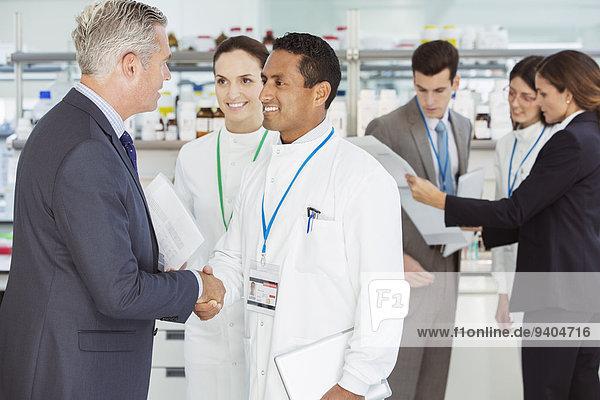 Wissenschaftler und Geschäftsmann beim Händeschütteln im Labor