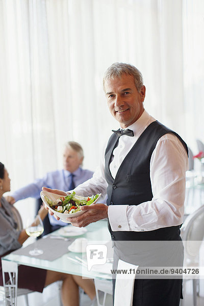Porträt des Kellners mit Salatschüssel  Menschen am Tisch im Hintergrund