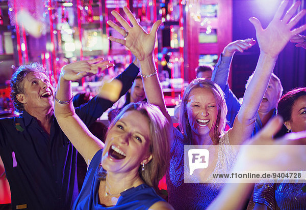 People raising hands and laughing in nightclub