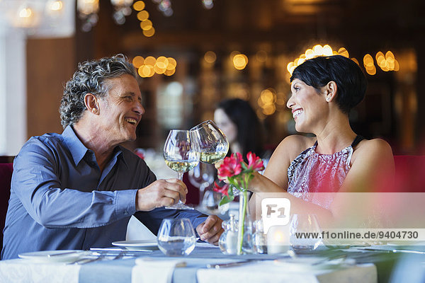 Smiling mature couple raising toast with white wine at restaurant table