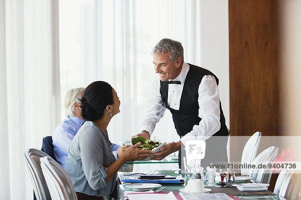 Lächelnder Kellner serviert Salat an eine Frau  die am Tisch im Restaurant sitzt.