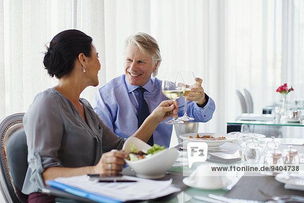 Lächelndes reifes Paar  das mit Weißwein am Restauranttisch anstößt.
