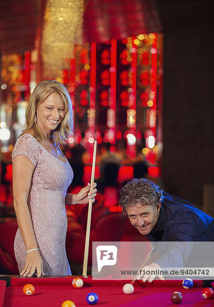 Woman and man playing pool in bar