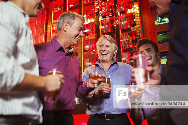Group of smiling men having drink in bar