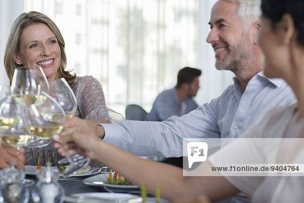 People raising a toast with white wine in restaurant