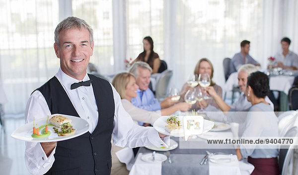 Porträt des Kellners  der den Teller mit ausgefallenen Gerichten hält  Menschen an Restauranttischen im Hintergrund