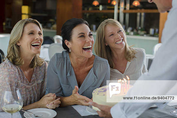 Man handing birthday cake to women