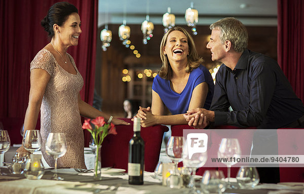 Man and women smiling at talking in elegant restaurant