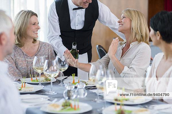 Kellnerin  die der Kundin am Restauranttisch Wein anbietet  Frau  die sich weigert.