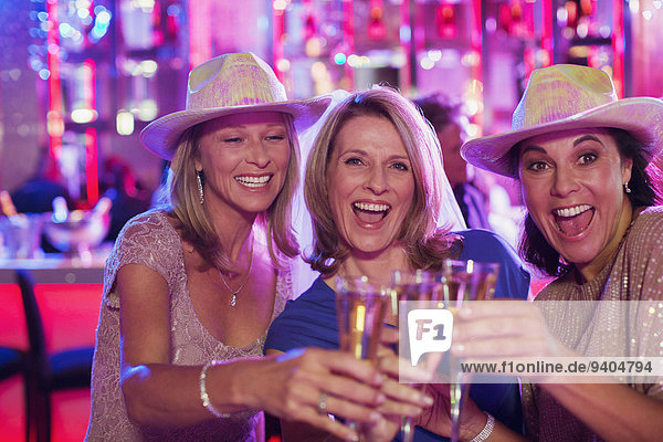 Portrait of three cheerful women wearing cowboy hats toasting with champagne flutes in nightclub
