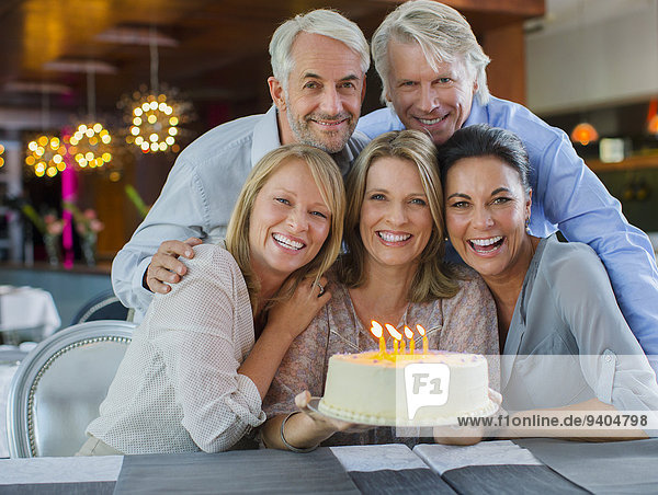 Portrait of smiling mature men and women with birthday cake