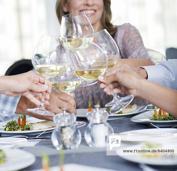 People toasting with white wine in restaurant