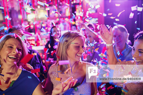 Confetti falling on smiling mature women dancing in nightclub