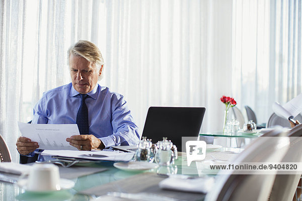 Businessman looking at chart at restaurant table