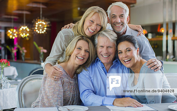 Portrait of smiling mature men and women sitting at restaurant table