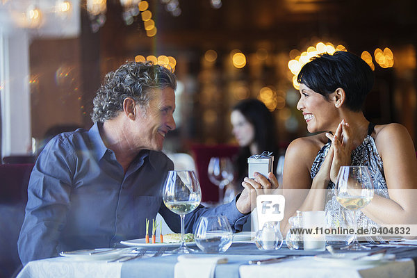 Mature man giving gift to smiling woman in restaurant