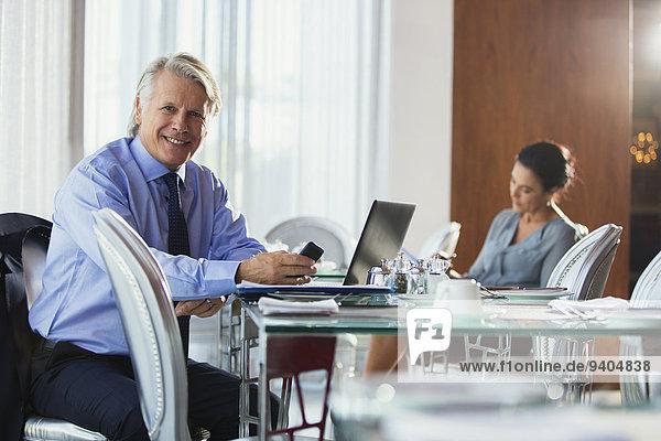 Portrait des lächelnden Geschäftsmannes mit Smartphone und Laptop im Restaurant