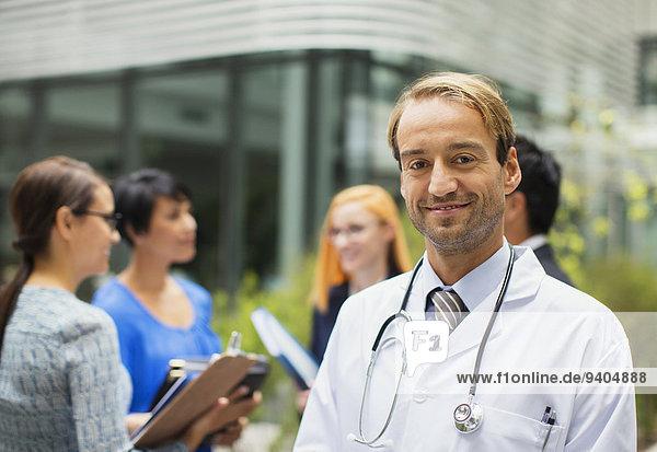 Porträt eines lächelnden Arztes im Laborkittel vor dem Krankenhaus  Frauen mit Klemmbrettern im Hintergrund