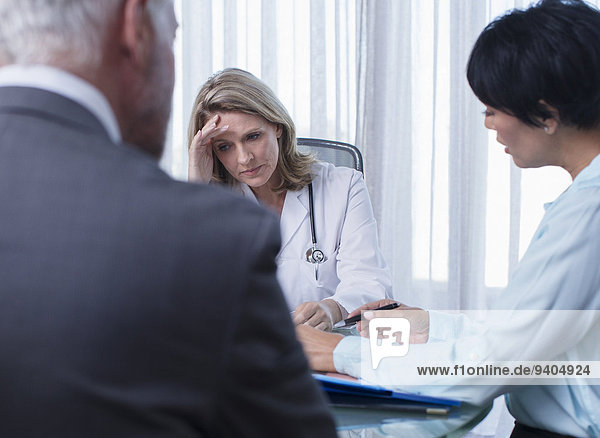 Ärztin  Mann und Frau beim Gespräch am Tisch im Konferenzraum