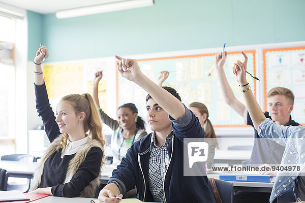 Students raising arms during lesson in classroom