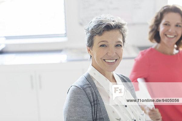 Porträt einer lächelnden reifen Geschäftsfrau mit Kollegin im Hintergrund