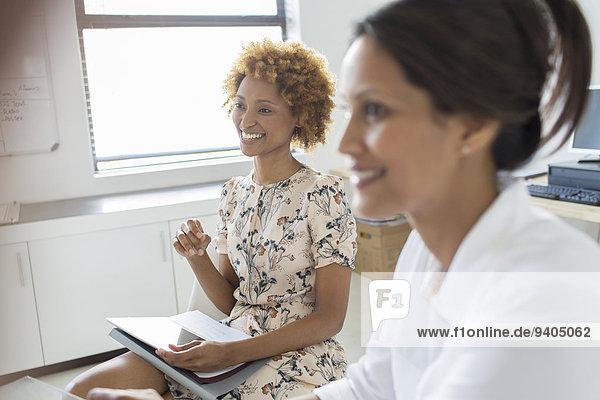 Zwei lächelnde Geschäftsfrauen bei der Besprechung im Büro
