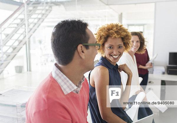 Gruppe von lächelnden Geschäftsleuten  die sich im Büro treffen