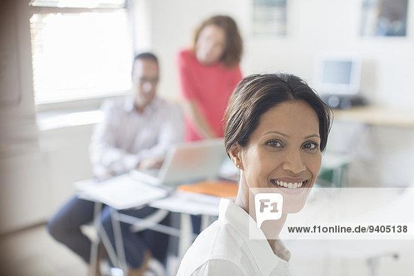Porträt einer lächelnden Geschäftsfrau im Büro  Kollegen im Hintergrund