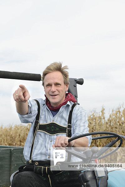 Mature man on tractor in cornfield