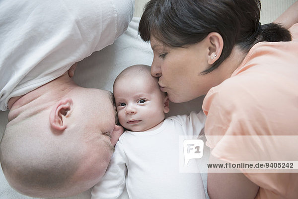 Parents kissing their baby boy  close up