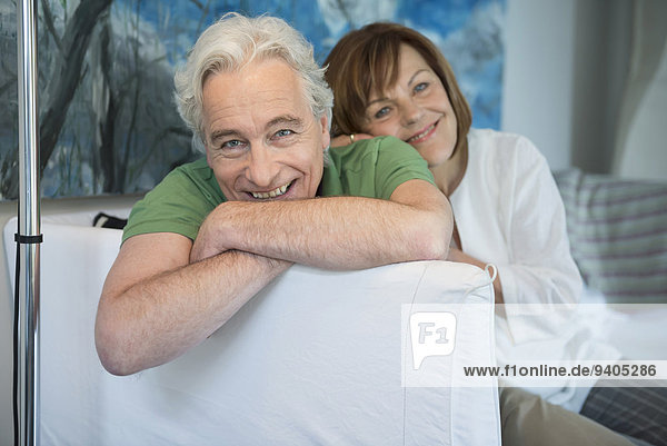 Portrait of couple sitting on couch in living room  smiling