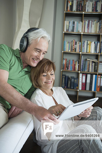 Couple using digital tablet while man with headset  smiling