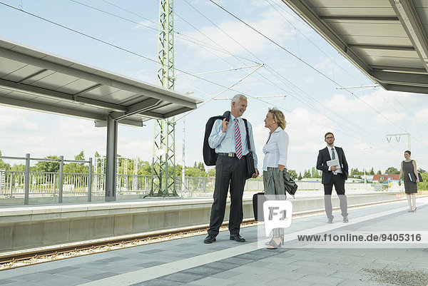 Four businessmen waiting for train