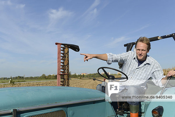 Farmer sitting on tractor and pointing somewhere