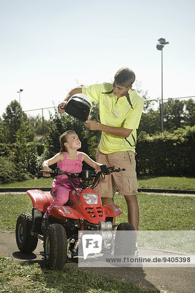 Tutor assisting girl with helmet on driver training area