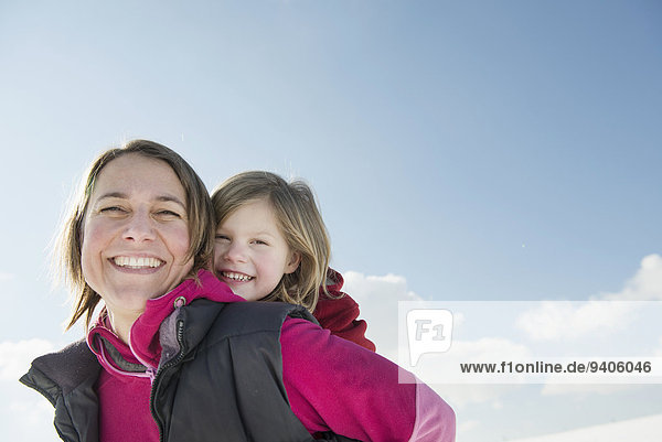 Mother giving piggyback ride to daughter  smiling