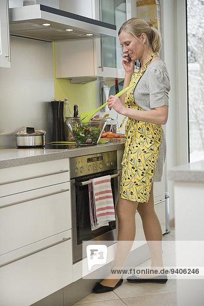 Frau sprechen Vorbereitung Küche Salat telefoniert
