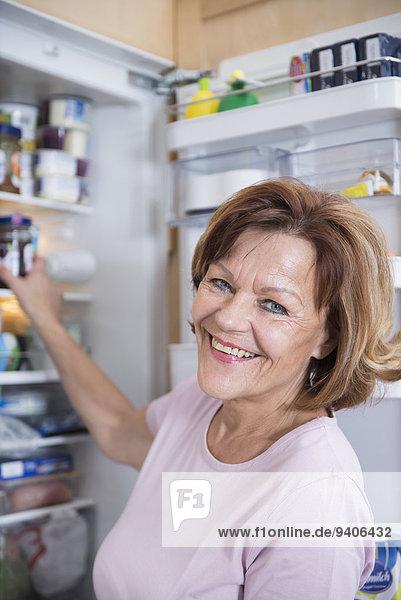 Senior Senioren Portrait Frau lächeln offen Kühlschrank