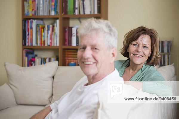 sitzend Senior Senioren Portrait lächeln Zimmer Couch Wohnzimmer