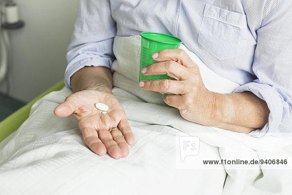 Patientin Tasse Krankenhaus halten Pille